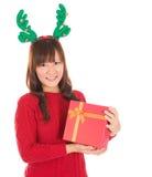 拿着礼物佩带的驯鹿垫铁的亚裔圣诞节妇女。 库存图片
