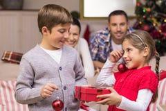 拿着礼物和中看不中用的物品的兄弟和姐妹 免版税库存照片