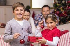 拿着礼物和中看不中用的物品的微笑的兄弟和姐妹 免版税图库摄影