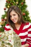 拿着礼物圣诞树背景的美丽的女孩 免版税图库摄影
