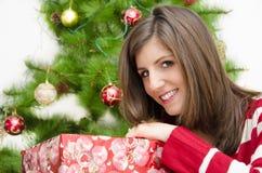 拿着礼物圣诞树背景2的美丽的女孩 库存图片