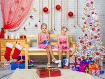 拿着礼物在他们的手上的愉快的姐妹,和坐在圣诞节设置的一条长凳 库存图片