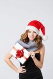 拿着礼物的一件黑礼服和圣诞老人帽子的美丽的妇女 库存照片