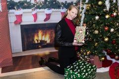 拿着礼物的假日场面的白肤金发的女性在树旁边 图库摄影