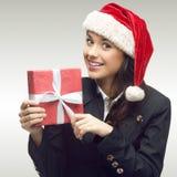 拿着礼物的圣诞老人帽子的女商人 免版税库存图片