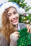 拿着礼物的圣诞老人帽子的愉快的微笑的白种人妇女在手中请求 库存图片