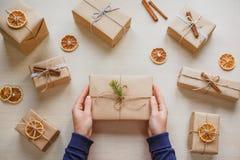 拿着礼物的妇女在一张木桌放置了 库存照片