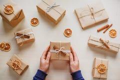 拿着礼物的妇女在一张木桌放置了 免版税库存照片