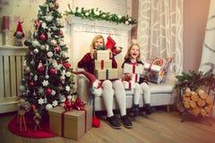 拿着礼物的小女孩由圣诞树 免版税库存照片