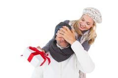 拿着礼物的愉快的妇女,当盖丈夫时注视 免版税库存照片