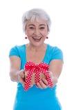拿着礼物的愉快的被隔绝的老妇人。 免版税库存照片