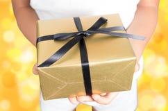 拿着礼物的手被包裹在金黄 免版税库存照片