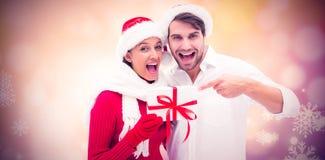拿着礼物的欢乐年轻夫妇的综合图象 免版税库存图片
