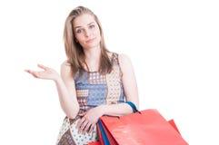 拿着礼物的现代衣裳的可爱的购物妇女请求 免版税库存图片