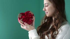 拿着礼物的美丽的女孩以与一把红色弓的心脏的形式 影视素材