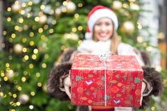 拿着礼物的美丽的微笑的妇女入照相机 库存图片