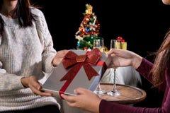 拿着礼物盒和两块玻璃与可汗的美丽的两名妇女 免版税库存图片