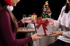 拿着礼物盒和两块玻璃与可汗的美丽的两名妇女 免版税库存照片