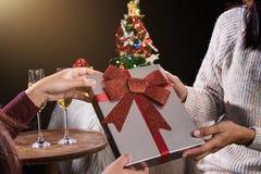 拿着礼物盒和两块玻璃与可汗的美丽的两名妇女 库存图片