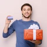 拿着礼物盒和信用卡的年轻人画象。Handso 免版税库存图片
