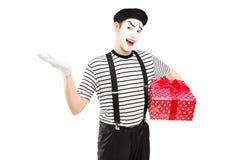拿着礼物盒和打手势用他的手的男性笑剧艺术家 免版税图库摄影