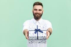 拿着礼物盒和看照相机和暴牙的微笑的商人 库存照片