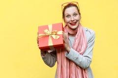 拿着礼物盒和看照相机的年轻妇女和也是 免版税库存图片