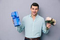拿着礼物盒和花的年轻偶然人 库存图片