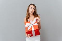 拿着礼物盒的一名沉思想知道的妇女的画象 免版税库存照片
