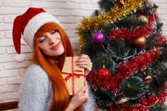 拿着礼物盒的圣诞老人盖帽的美丽的年轻红头发人女孩坐 库存照片