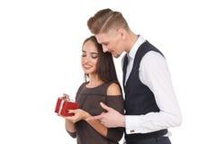 拿着礼物盒的女孩,人拥抱女孩从后面 查出 免版税库存图片