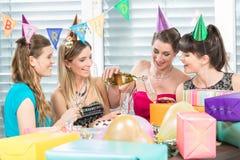拿着礼物盒的快乐的妇女在惊奇生日聚会期间 免版税库存照片