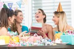 拿着礼物盒的快乐的妇女在惊奇生日聚会期间 免版税图库摄影