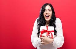 拿着礼物盒的愉快的少妇 免版税库存照片