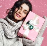 拿着礼物盒的毛线衣和手套的微笑的少女 库存照片