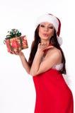 拿着礼物盒的美丽的深色的圣诞老人女孩。 免版税库存照片