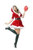 拿着礼物盒的跳跃的激动的圣诞老人妇女的空中行动 库存照片