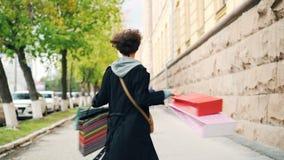 拿着礼物袋子和转动看的激动的女孩慢动作画象获得的照相机乐趣 购物,青年时期 股票录像