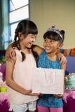 拿着礼物袋子的孩子在生日聚会期间 免版税库存图片