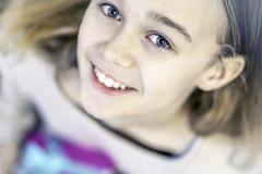 拿着礼物,微笑和看照相机的逗人喜爱的少女 库存照片