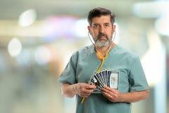 拿着社会保险卡和听诊器的西班牙医生 免版税库存照片