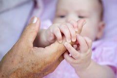 拿着祖母的婴孩手 免版税图库摄影