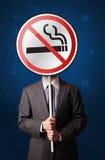 拿着禁烟标志的商人 免版税库存照片