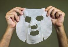 拿着秀丽纸面膜的人手被隔绝在面孔皮肤护理概念的甚而背景 免版税库存照片