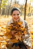 拿着秋叶的微笑的妇女 库存照片