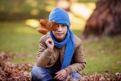 拿着秋天叶子的男孩画象 图库摄影