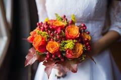 拿着秋天的婚姻的五颜六色的花束新娘开花 免版税库存图片