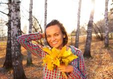 拿着秋天的花束青少年的女孩妇女 免版税图库摄影