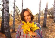 拿着秋天的花束青少年的女孩妇女 库存照片