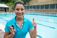 拿着秒表和显示赞许的游泳教练画象临近游泳池边 库存图片